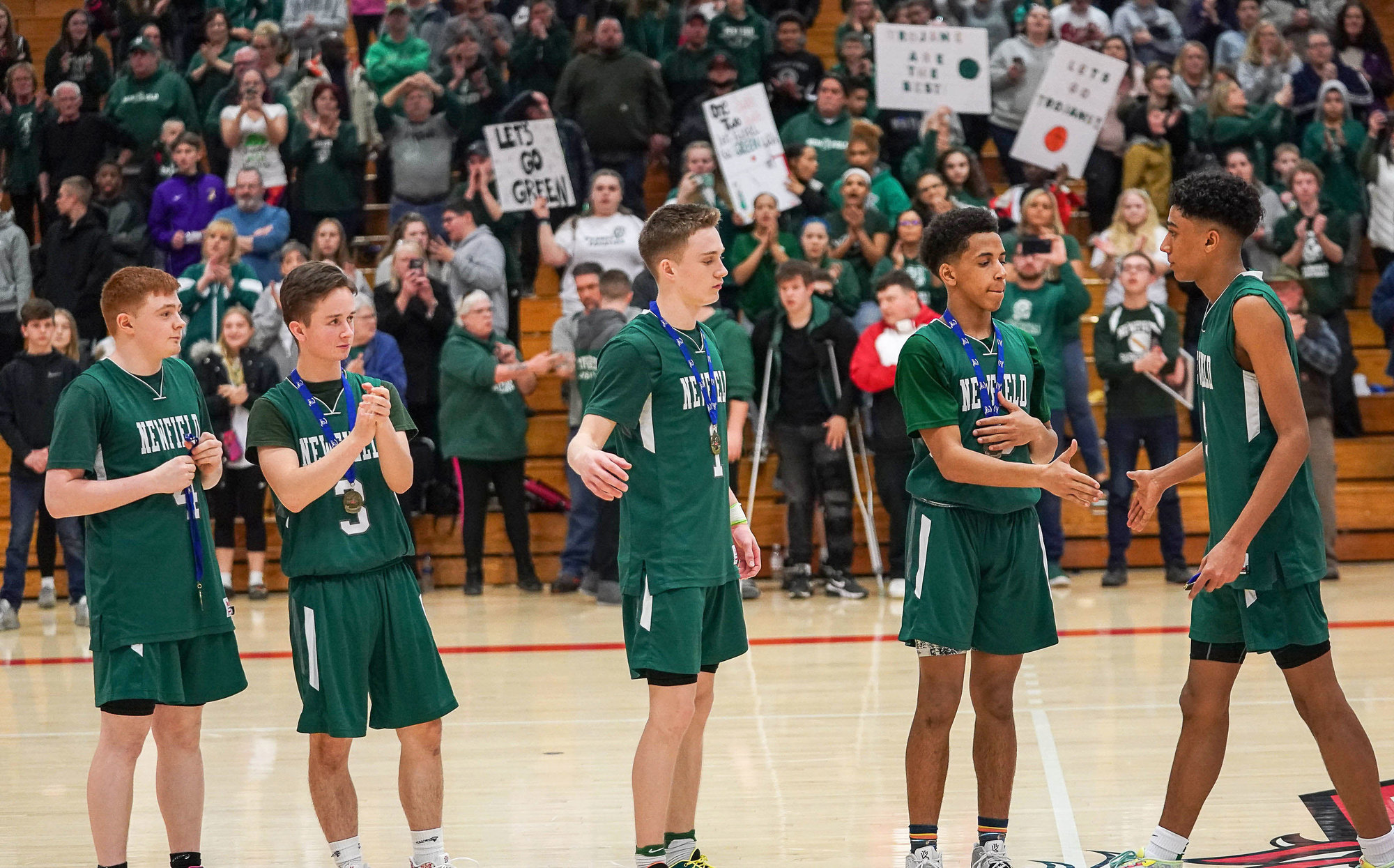 (From left to right) Newfield basketball players Dylan Zifchock, Alex Schwoeble, Jacob Humble, Jalen Hardison, and Daejahd Leckey receive their Section IV Championship medals in front of fans. It is the Trojans' third Section IV title in four years.