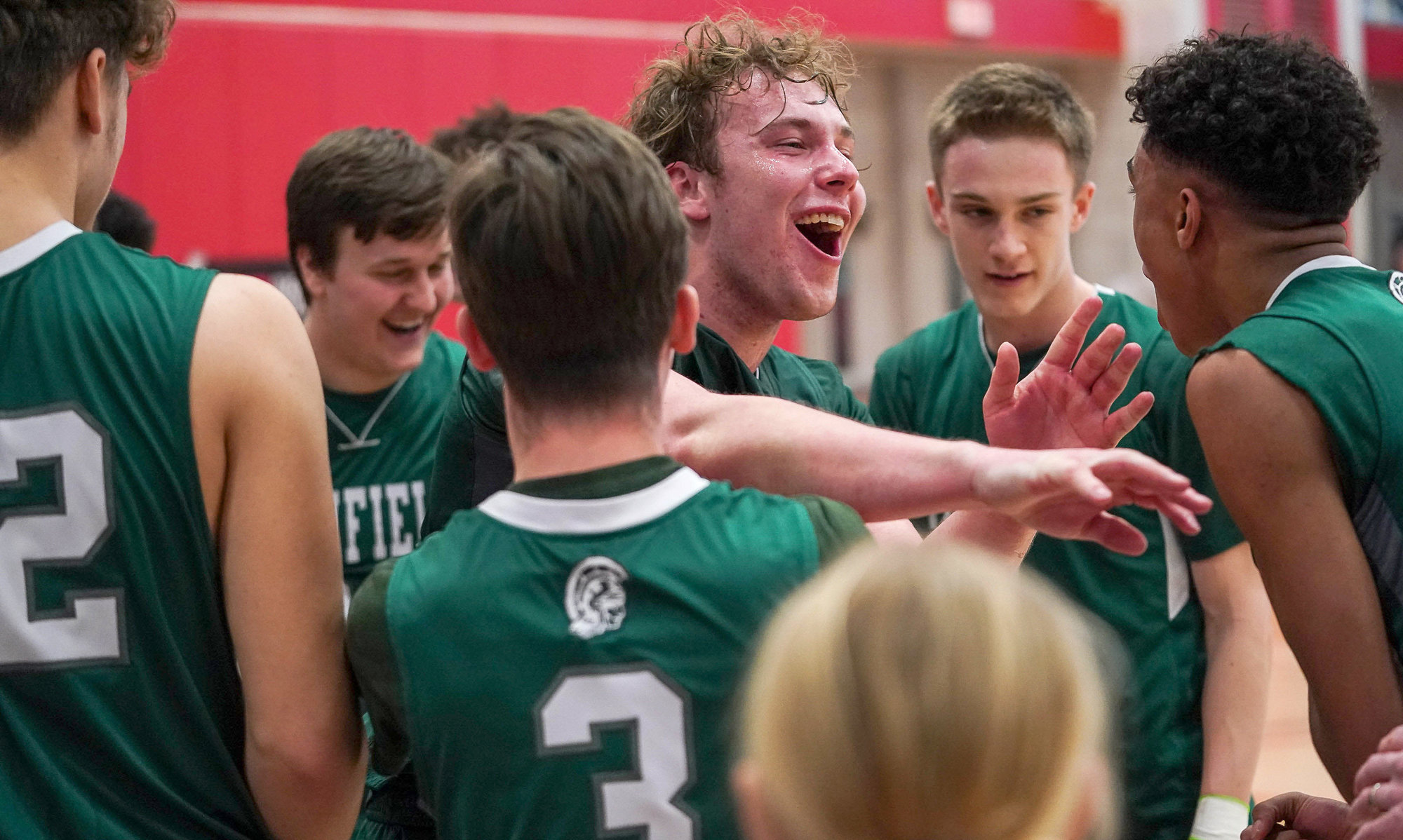 Josh Wood (center) and teammates celebrate Newfield's 63-60 victory over Watkins Glen in the Section IV Championship game. It is the Trojans' third Section IV title in four years.