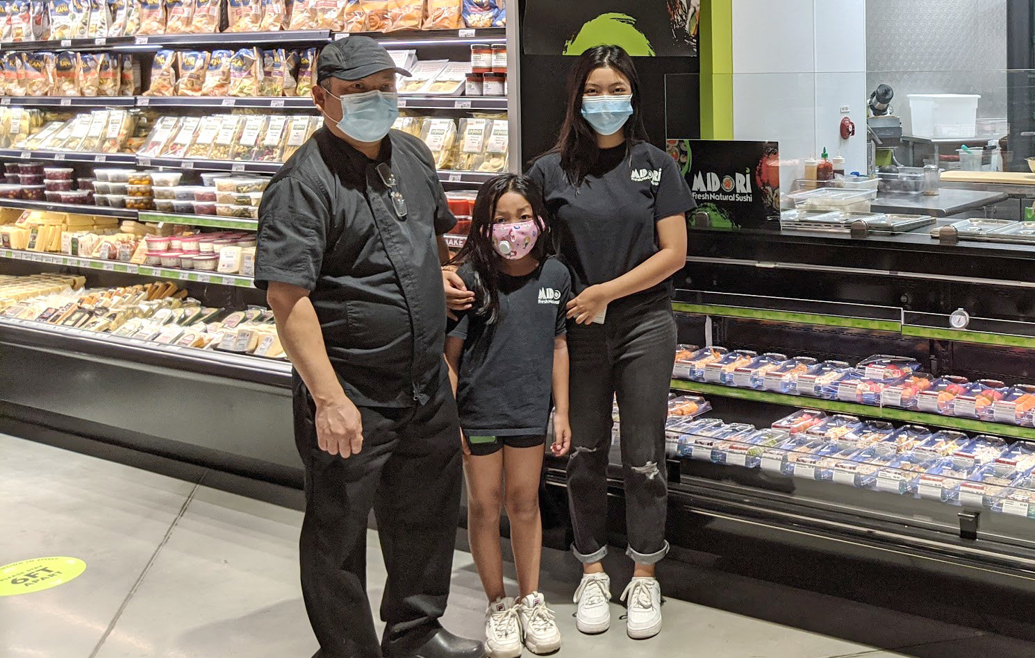 Midori Sushi Owner Ye Myint stands in front of his family's sushi bar inside GreenStar's new store with his two daughters, Thone Myint (center) and Haythi Myint.