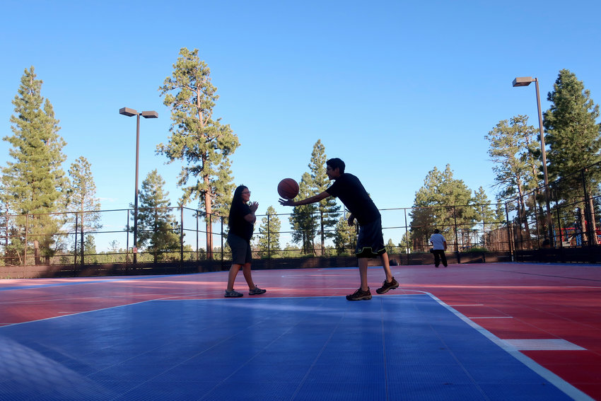 Doria Kootswatewa, left, and her boyfriend, Paul Rogers, right, play basketball at a sports complex July 28, 2020 in Tusayan. [Felicia Fonseca/The Associated Press]