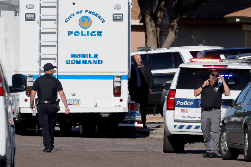 Law enforcement officers stand outside the scene of a deadly shooting early Monday, March 30, 2020, in Phoenix. [Matt York/The Associated Press]