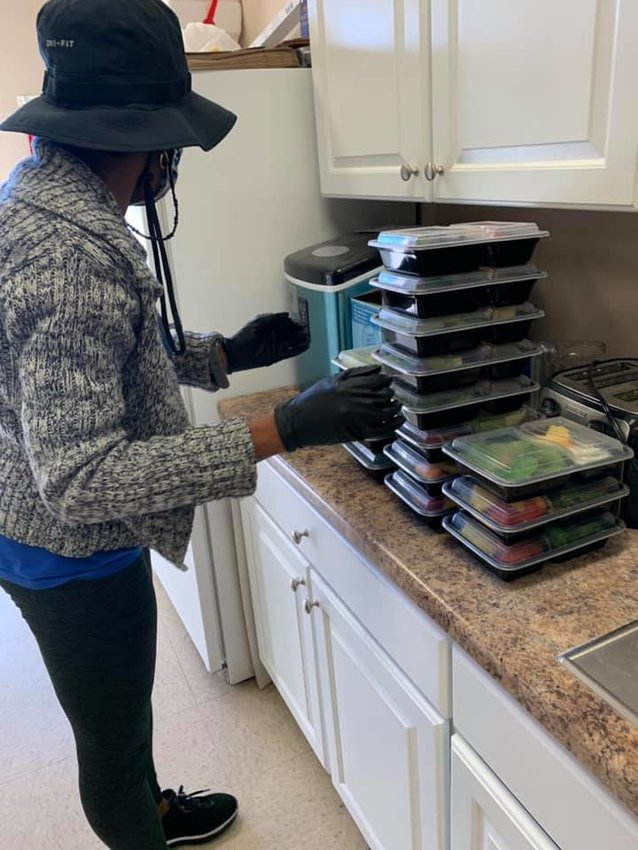 A volunteer preps checks meals to be delivered.