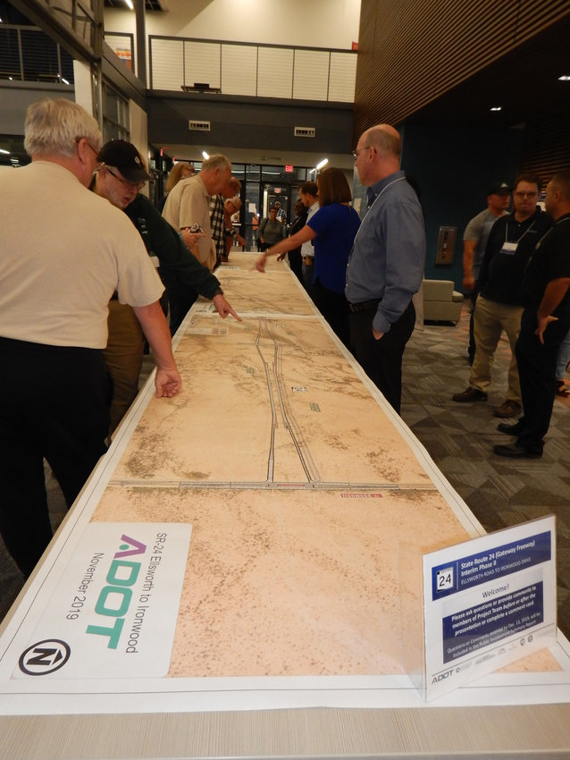 Area residents view a map of the proposed State Route 24 route on a table.