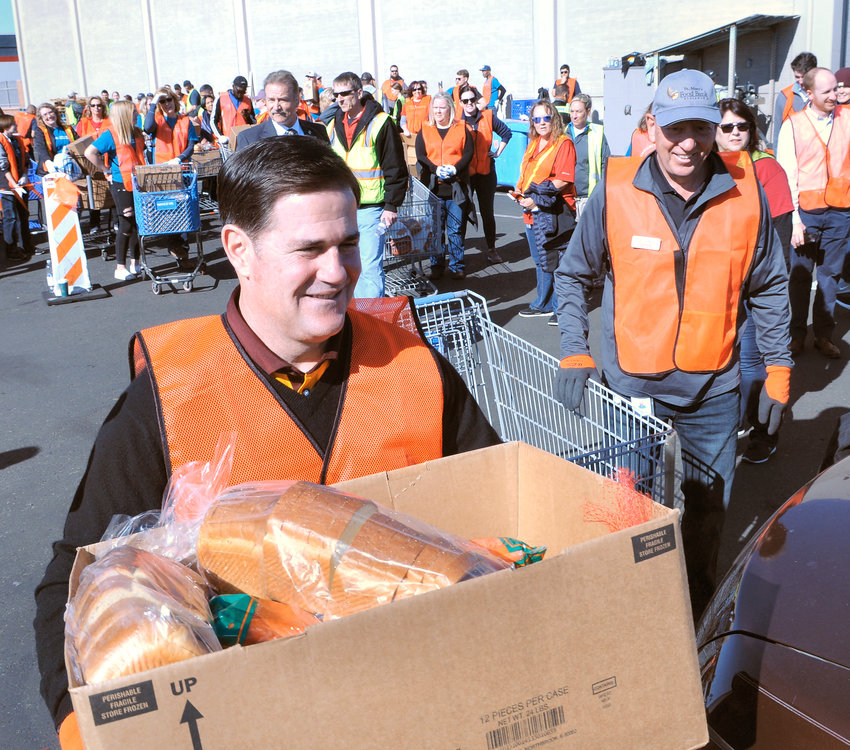 In this Nov. 26 file photo, Gov. Doug Ducey helps load food baskets into waiting cars Tuesday at St. Mary's Food Bank in Phoenix. The governor this week responded to a presidential executive order with a letter to Secretary of State Mike Pompeo, saying Arizona will continue to welcome refugees fleeing religious and political persecution.