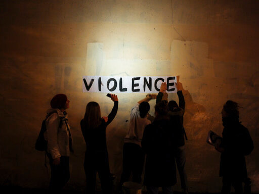 """Under cover of night, activists have glued the word """"violence"""" to walls in Paris to draw attention to domestic violence. In Arizona, a new order of protection system will give victims an easier way to protect themselves against their alleged abusers."""