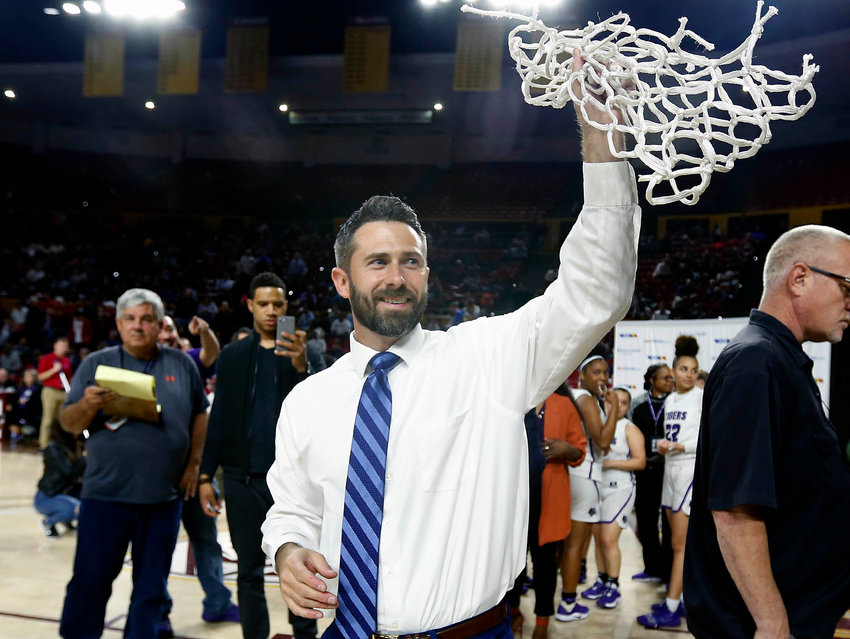 Millennium head coach Courtland Rojeck holds up the basketball net as he acknowledges the crowd following a 59-30 victory over Sunrise Mountain to win the 5A girls basketball state championship in Tempe on Monday, March 2, 2020.  (Ralph Freso for West Valley Preps)