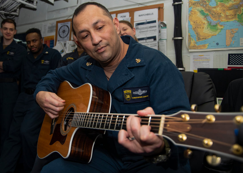 U.S. Navy Chief Information Systems Technician Christopher Garcia, from Phoenix, plays guitar aboard the aircraft carrier USS Harry S. Truman (CVN 75) in the Arabian Sea.