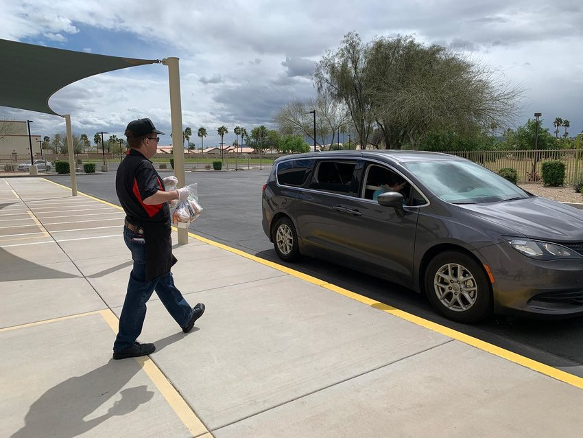An Avondale Elementary School District employee takes grab-and-go meal bags to a family March 20.