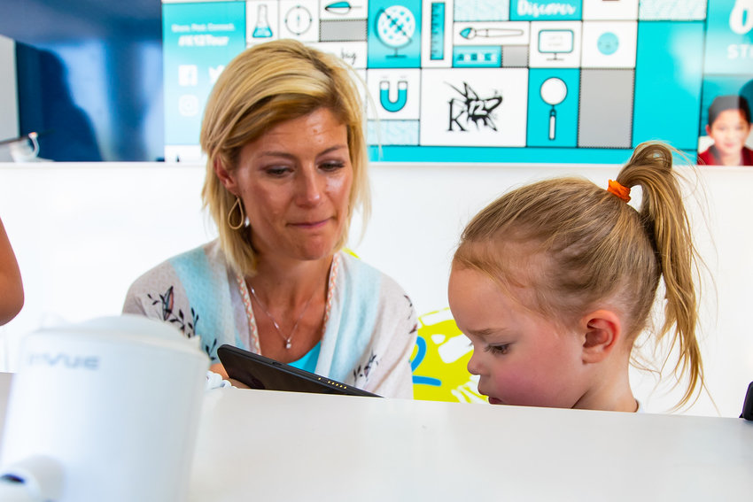 Seraphina Ross and Banji Judge, principal of QC Learning Center play an educational game on a tablet.