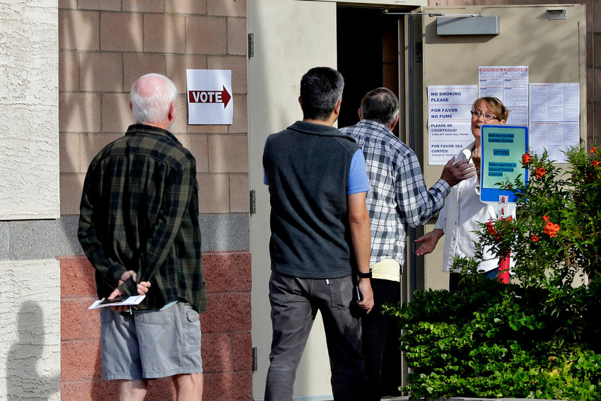 Arizona voters are held outside until other voters leave the polling station prior to casting their ballot in the Arizona presidential preference election Tuesday, March 17, 2020, in Phoenix.