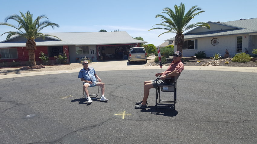 Two men sit six feet apart as they visit in their cul-de-sac in Sun City.