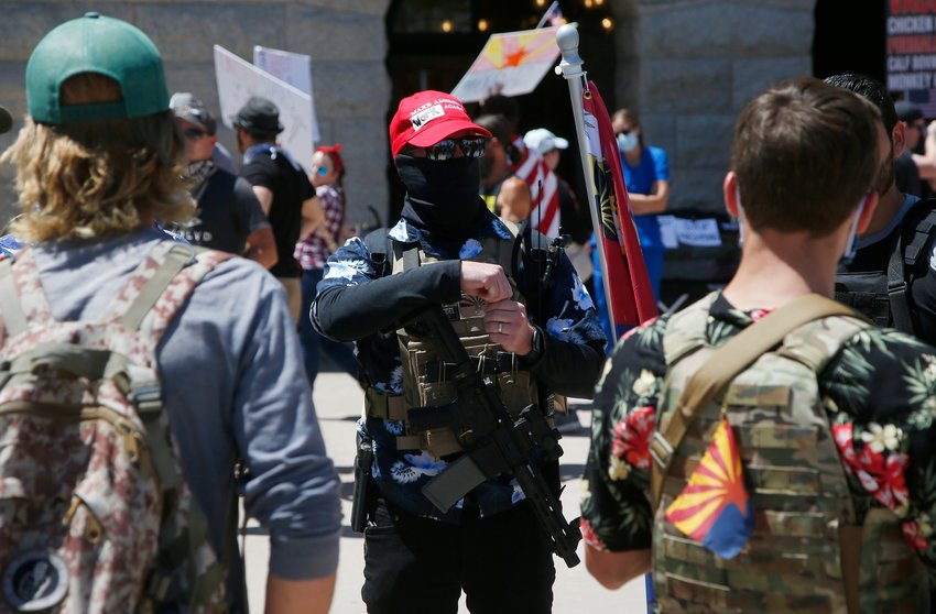 Protesters carrying weapons rally at the state Capitol to 're-open' Arizona against the governor's stay-at-home order due to the coronavirus Monday, April 20, 2020, in Phoenix. A bill working its way through the Legislature could make it a crime to be at a protest if a riot breaks out.