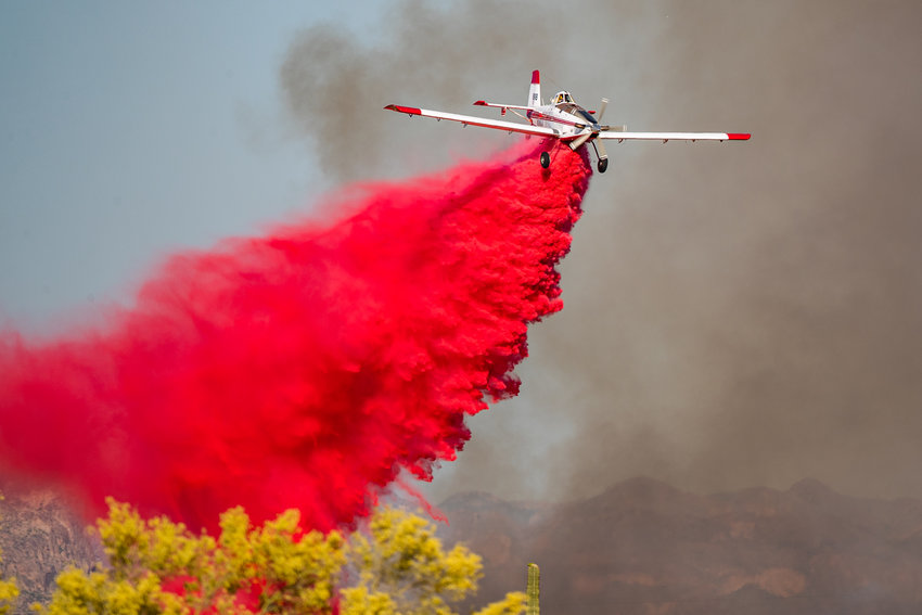 A plane drops fire retardant May 7 at the Southern Fire in Apache Junction.