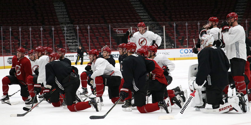 Coyotes players huddle on the ice during a practice at Gila River Arena in Glendale before the NHL season was postponed on March 12. Among the things Coyotes player say they miss most during the postponement of the NHL season is the camaraderie with teammates. [Jenna Ortiz/Cronkite News]