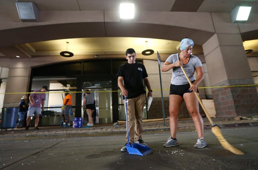 Volunteers help sweep up broken glass from the vandalism damage at Scottsdale Fashion Square Mall Sunday, May 31, in Scottsdale, Ariz., following a night of unrest and protests over the death of George Floyd, a handcuffed black man who died in police custody with much of the arrest captured on video of a Minneapolis police officer kneeling on the neck of Floyd.