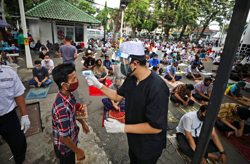 A mosque official takes the temperature reading of a man entering the Cut Meutia mosque to attend a Friday prayer amid concerns of coronavirus outbreak in Jakarta, Indonesia, Friday, June 5, 2020. Muslims in Indonesia's capital held their first communal Friday prayers as mosques closed by the coronavirus outbreak for nine weeks reopened at half capacity. (AP Photo/Dita Alangkara)