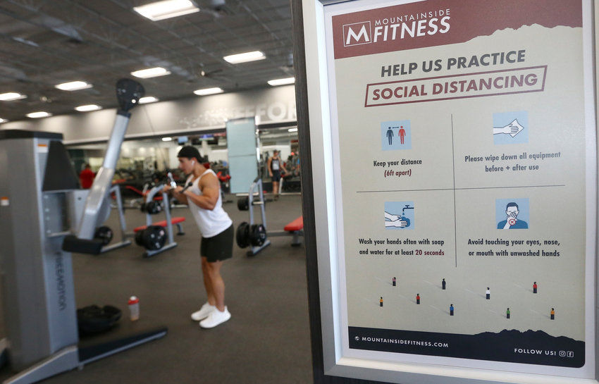 In this July 2, 2020, file photo, a client works out at Mountainside Fitness as the facility remains open even as Arizona Gov. Doug Ducey has issued an executive order for all gyms to close due to the surge in coronavirus cases in Phoenix.