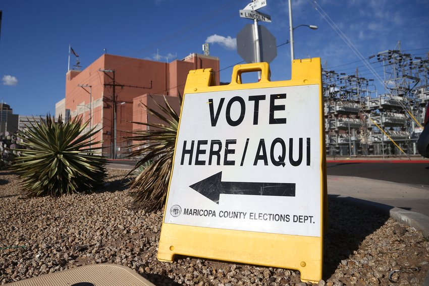 A sign points to a local polling station for the Arizona Democratic presidential preference election Tuesday, March 17, 2020, in Phoenix.