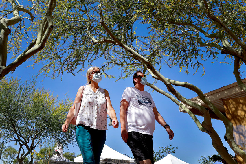 People wear masks to prevent the spread of coronavirus as they walk through the farmers market Saturday, April 25, 2020, in Gilbert, Arizona. Arizona Gov. Doug Ducey has rescinded his executive order allowing cities and counties to require masks, but several said they will continue to do so.