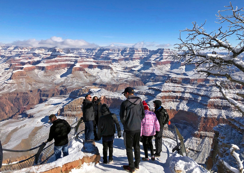In this Jan. 1, 2019 photo, tourists look at and take photos of a snow-covered Grand Canyon in Arizona. The Arizona Office of Tourism reports visitors to the state spent a record $25.6 billion in 2019.