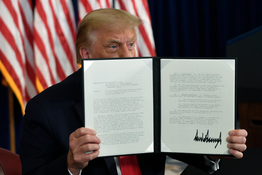 President Donald Trump signs an executive order during a news conference at the Trump National Golf Club in Bedminster, N.J., Saturday, Aug. 8, 2020. [The Associated Press]