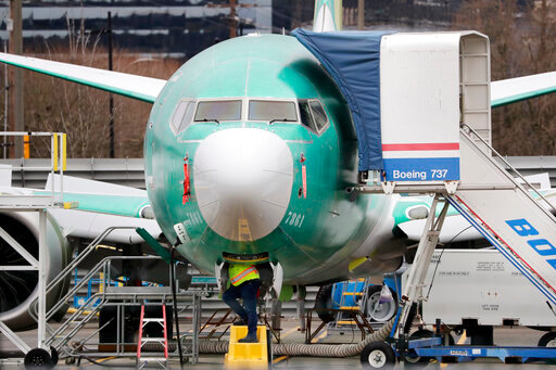 FILE - In this Dec. 16, 2019, file photo, a worker looks up underneath a Boeing 737 MAX jet, in Renton, Wash.  Boeing is reporting more weak numbers for airplane orders and deliveries. The big aircraft maker said Tuesday, Aug. 11, 2020 it it sold no new airliners in July, and customers canceled orders for 43 of its 737 Max jet. That's the plane that has been grounded for more than a year after two crashes killed 346 people.  (AP Photo/Elaine Thompson, File)