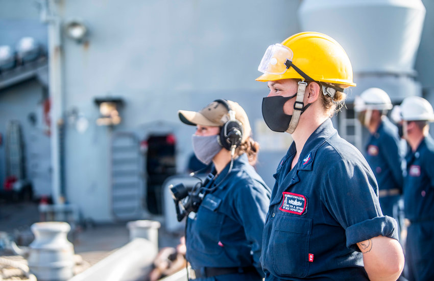 OKINAWA, Japan -- Boatswain's Mate 2nd Class Anjellica Beyner, from Orlando, Fla., right, and Seaman Lizzy Campos-Valdez, from Phoenix, man the rails on the fo'c'sle during a sea and anchor evolution aboard the amphibious dock landing ship USS Germantown (LSD 42).