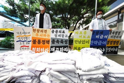 """Doctors hold signs criticizing the government's medical policy at a hospital in Suwon, South Korea, Wednesday, Aug. 26, 2020. Health officials in South Korea called on thousands of striking doctors to return to work as the country counted its 13th straight day of triple-digit daily jumps in coronavirus cases. The sign reads: """"Let's criticize the rapid administration and we oppose policies that ignore filed opinions and ensure working conditions."""" (Hong Hae-in/Yonhap via AP)"""