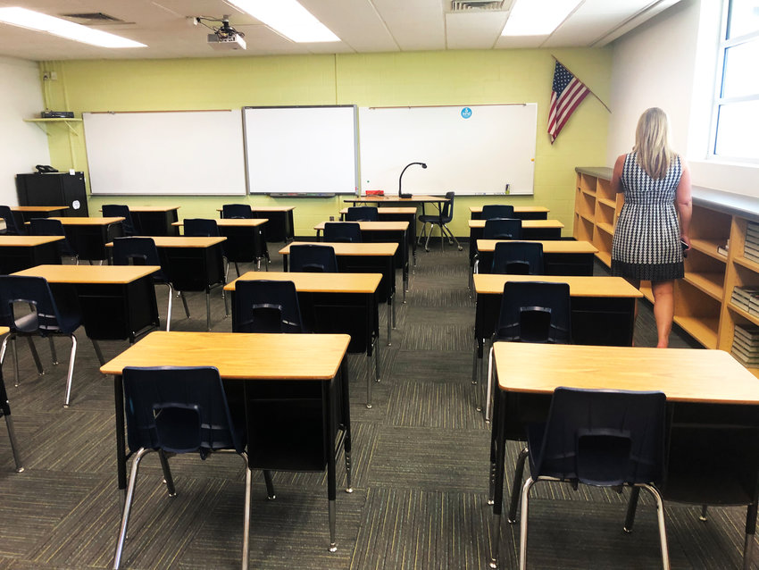 """A DVUSD staff member walks a new """"model"""" classroom. The district has reconfigured rooms in five schools with safety precautions to anticipate the return of students to campus."""