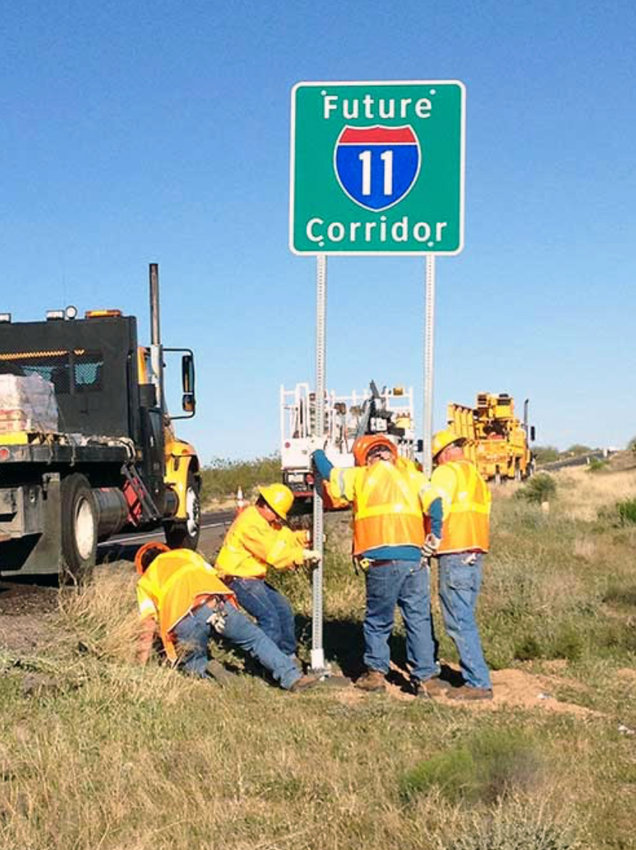 Workers from the Arizona Department of Transportation work to install one of four signs signaling the future route of Interstate 11 in 2014.