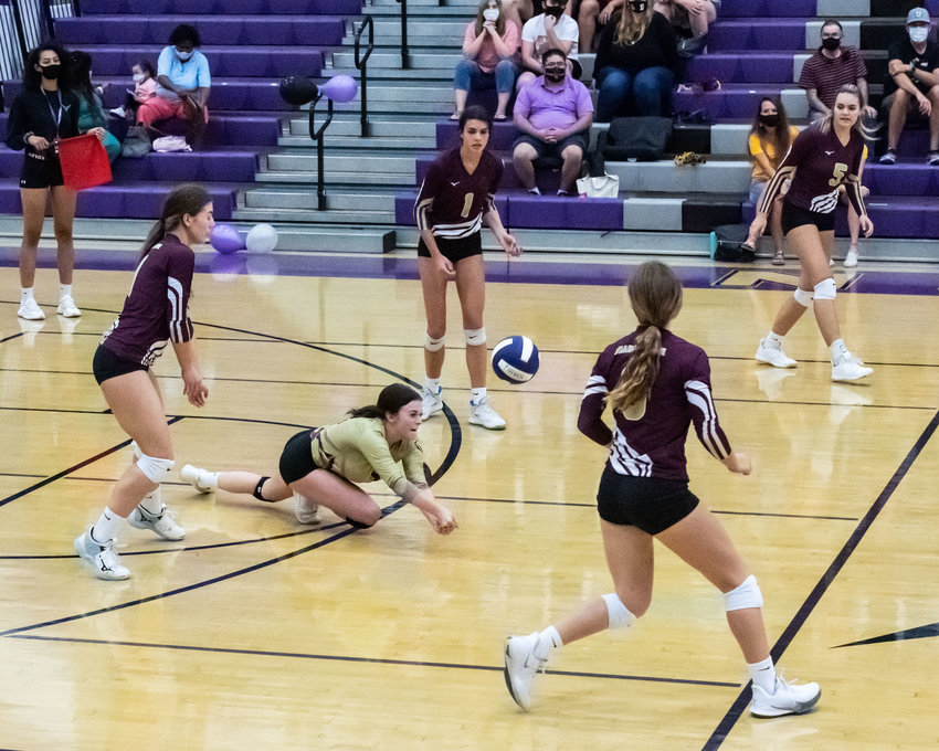 Shadow Ridge senior libero Taylor Reigelsperger lays out for a dig during a road match at Valley Vista Sept. 29. Home and visiting fans watch on socially distanced. Starting Monday, Feb. 8, the AIA will allow schools to admit visiting two parents/guardians per player at their discretion.