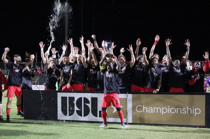 Phoenix Rising captain Solomon Asante, front, lifts the 2020 Western Conference Championship trophy as his teammates celebrate on Saturday night at Casino Arizona Field.