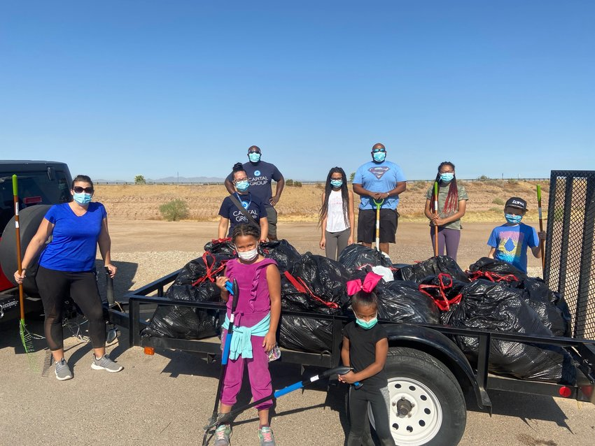 Members of the Brownlee and Okyere families with the bags of trash they hauled away from Tres Rios Base and Meridian Wildlife Area during a cleanup Oct. 18. Front, from left, are Alivia Brownlee, 7, and Zoe Okyere, 4. Back, from left, Joy Brownlee, Clare and Kofi Okyere, Mariah Brownlee, 10, Jerome Brownlee, Noelle Brownlee, 13, and Theo Richard, 9.