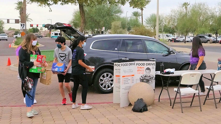 Volunteers accept a food donation Saturday, Oct. 24, at Fire Station 183 during Goodyear's Make a Difference Day food drive for St. Mary's Food Bank.