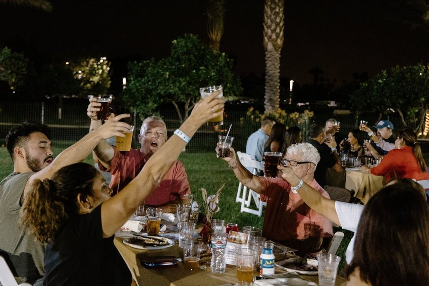 Oktoberfest attendees celebrate at their tables on the lawn at The Wigwam.