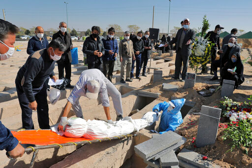 The body of a person who died from COVID-19 is interred as mourner look on, at the Behesht-e-Zahra cemetery on the outskirts of Tehran, Iran, Sunday, Nov. 1, 2020. The cemetery is struggling to keep up with the coronavirus pandemic ravaging Iran, with double the usual number of bodies arriving each day and grave diggers excavating thousands of new plots. (AP Photo/Ebrahim Noroozi)