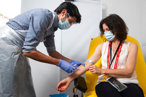 In this undated photo issued by the University of Oxford, a volunteer is administered the coronavirus vaccine developed by AstraZeneca and Oxford University, in Oxford, England. Pharmaceutical company AstraZeneca said Monday Nov. 23, 2020, that late-stage trials showed its coronavirus vaccine was up to 90% effective, giving public health officials hope they may soon have access to a vaccine that is cheaper and easier to distribute than some of its rivals. (University of Oxford/John Cairns via AP)