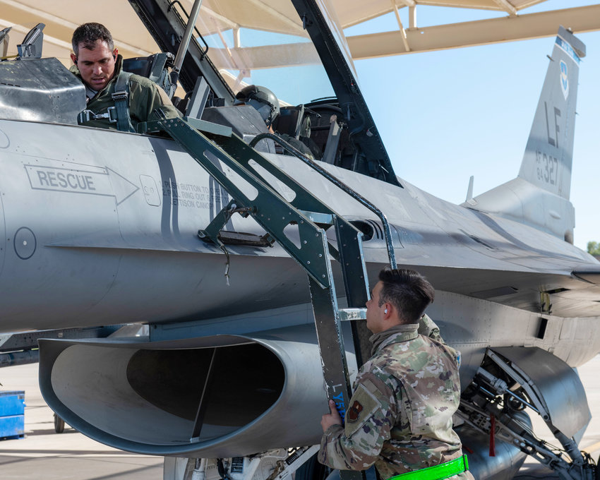 Airman 1st Class Erick Moreno, right, 372nd Training Squadron F-16 Fighting Falcon crew chief, prepares a 309th Fighter Squadron pilot for flight Nov. 17 at Luke Air Force Base.