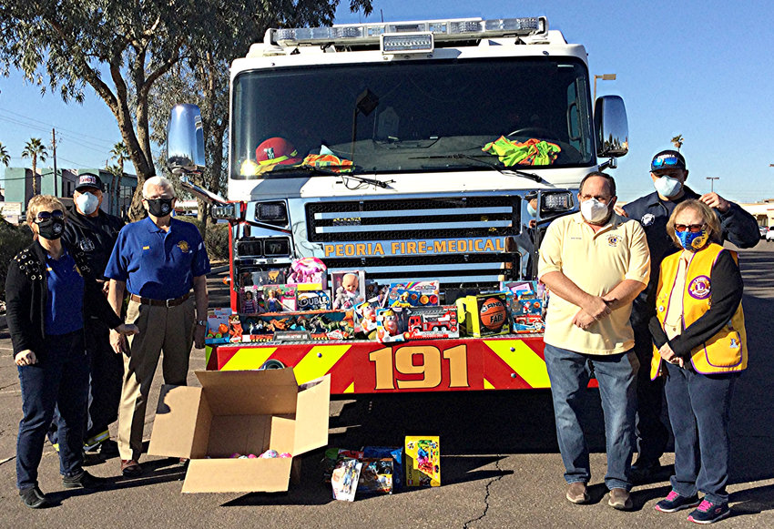 Lions Paul and Ellen Yopps, and Joyce and Rob Mayer pose with Peoria firefighters while donating toys for kids in need.