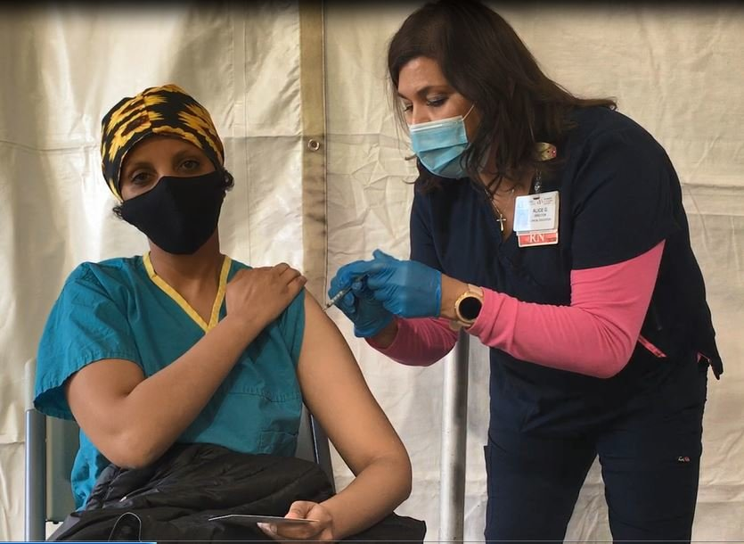 Alice Gonzales, RN, administers the COVID-19 vaccine to Dr. Emun Abdu at the point of dispensing POD at Abrazo West Campus in Goodyear, Dec. 21.