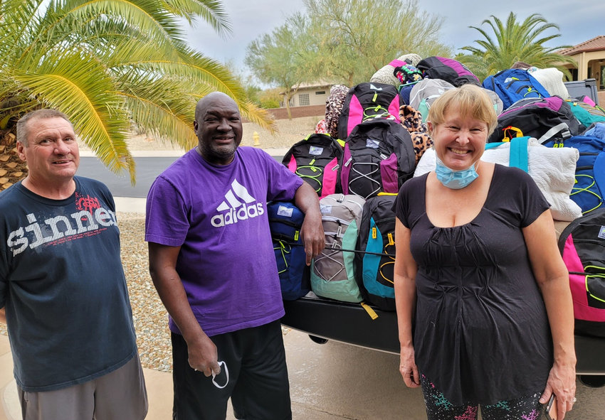 Grand Pickleball Club member Michael Wiebeto, left, Pastor Anthony Johnson of New Beginning Worship Center, middle and Grand Pickleball Club member Susan Konz stand in front of 100 backbacks filled with essentials collected by the Sun City Grand club for homeless in the community.