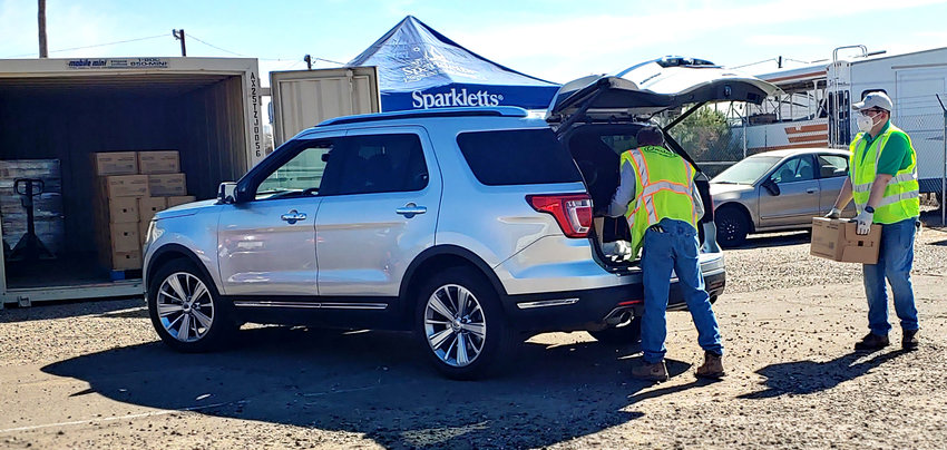 Luke personnel add boxes of bottled water to a resident's car on Feb. 23 at the pick-up site on the base in west Glendale.