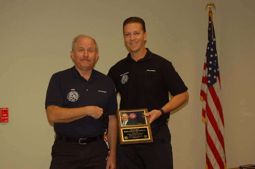 Ron Deadman, left, Sun City fire chief, receives a plaque from Rob Schmitz, assistant fire chief, recognizing the former's retirement from the fire service.