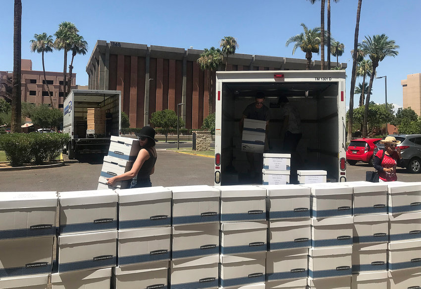 Supporters of the Outlaw Dirty Money ballot initiative unpack boxes of petitions to bring to the Arizona Secretary of State's office in Phoenix, Thursday, July 5, 2018. On Thursday, the Arizona Legislature advanced two measures designed to make it more difficult for public initiatives to find their way on the ballot and pass. (AP Photo/Melissa Daniels)