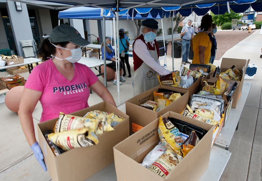 Volunteers from Phoenix College prep St. Mary's Food Bank donated food boxes as they load up vehicles in a drive thru set up at the Phoenix College campus due to the coronavirus Wednesday, April 8, 2020, in Phoenix, Ariz. (AP Photo/Ross D. Franklin)