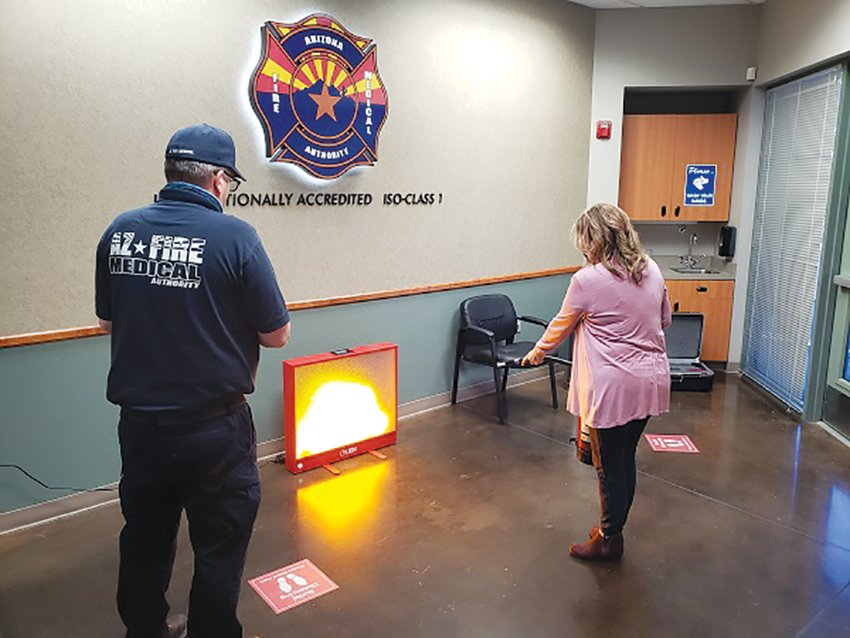 Jan Williams with the Arizona Fire & Medical Authority, 18818 N. Spanish Garden Drive, practices with the LION Bullseye digital fire extinguisher training system alongside John Teixeira, AFMA assistant fire marshall.