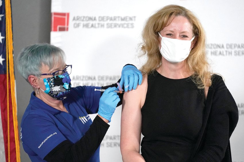 Dr. Cara Christ, right, director for the Arizona Department of Health Services, receives one of the first doses of the Pfizer-BioNTech vaccine for COVID-19 at the Arizona Department of Health Services State Laboratory from nurse Machrina Leach, Dec. 16, 2020, in Phoenix. Dr. Christ said soon appointments won't be needed to get a vaccine. [Ross D. Franklin/The Associated Press]