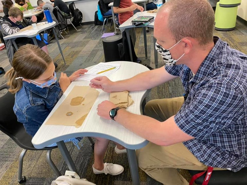 Sixth-grade science teacher Matthew Hinds works with a student at Belen Soto Elementary School in Goodyear recently.