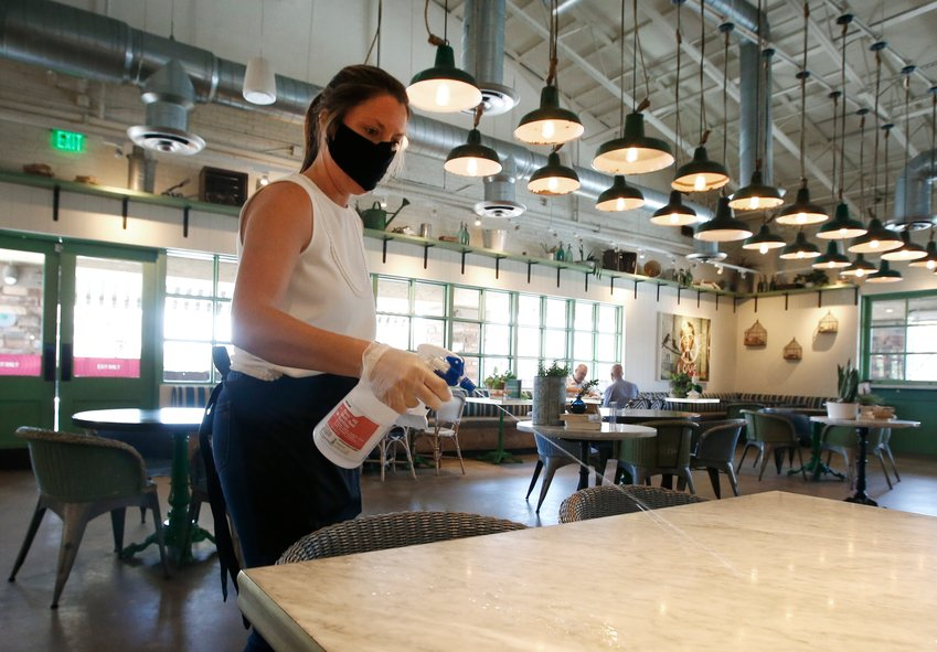 Laura Spencer, a recruiter at the corporate offices of the Fox Restaurant Concepts Phoenix-based eateries, cleans off a dining table as she helps out at Flower Child restauran Monday, May 11, 2020, in Phoenix. Arizona restaurants were among those posting hiring gains in April. (AP Photo/Ross D. Franklin)
