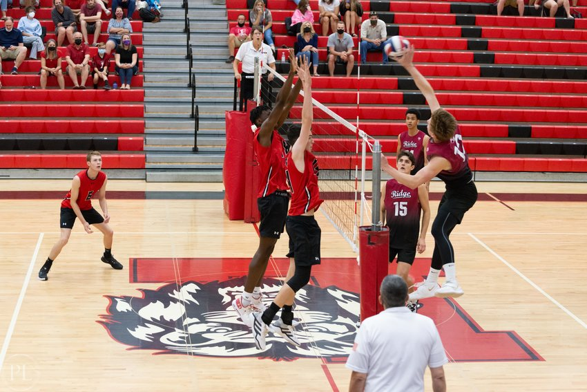 Mountain Ridge senior outside hitter Mason Henkels attacks against the Liberty block of sophomore Dane Schneberger (#14) and senior Ikenna Obi (#18). Henkels is the West Valley Preps boys volleyball player of the year.
